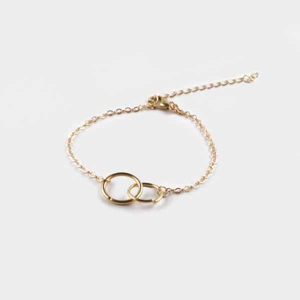 Petit bracelet dorée avec 2 anneaux qui s'entrecroisent