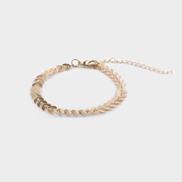 Un bracelet dorée en forme de feuillage